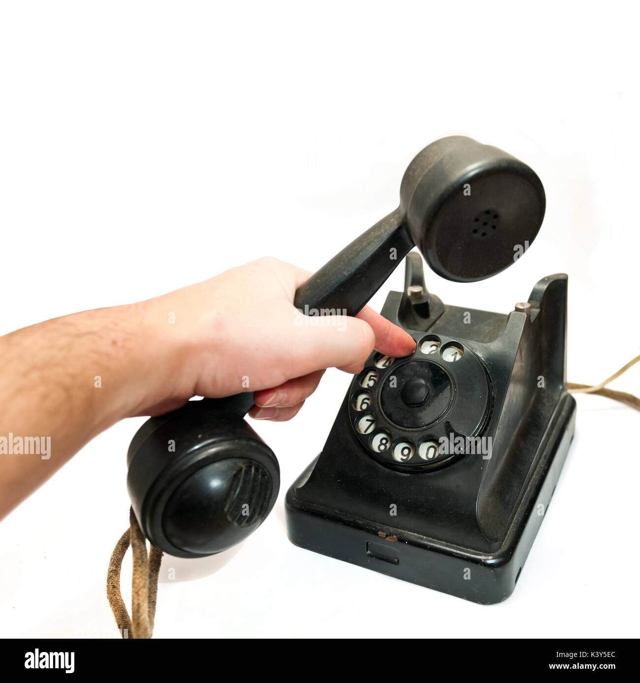 man hand hanging up the handset of an old black telephone - Stock Image