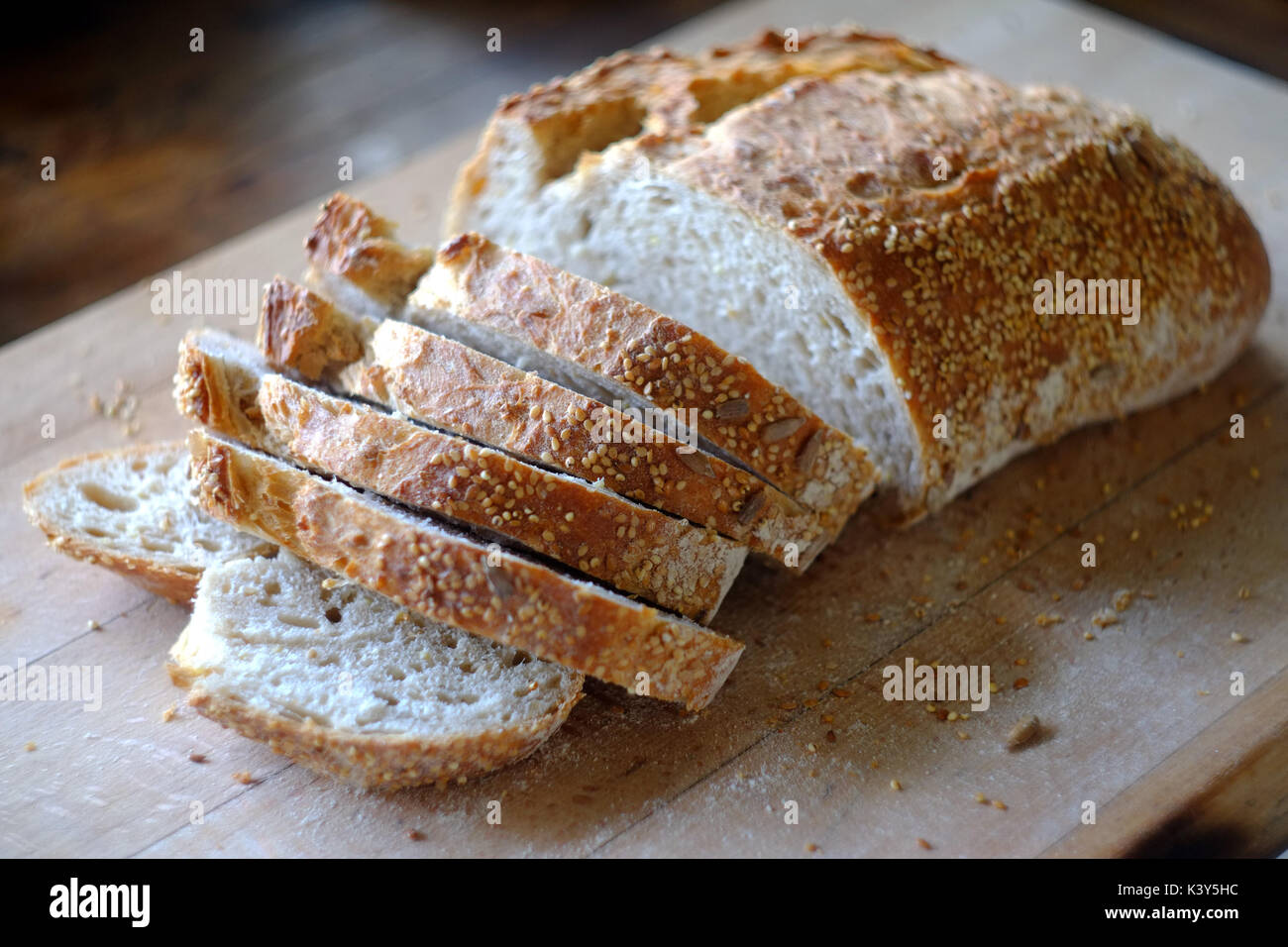 Fresh loaf of artisan bread being sliced on a wooden board. - Stock Image
