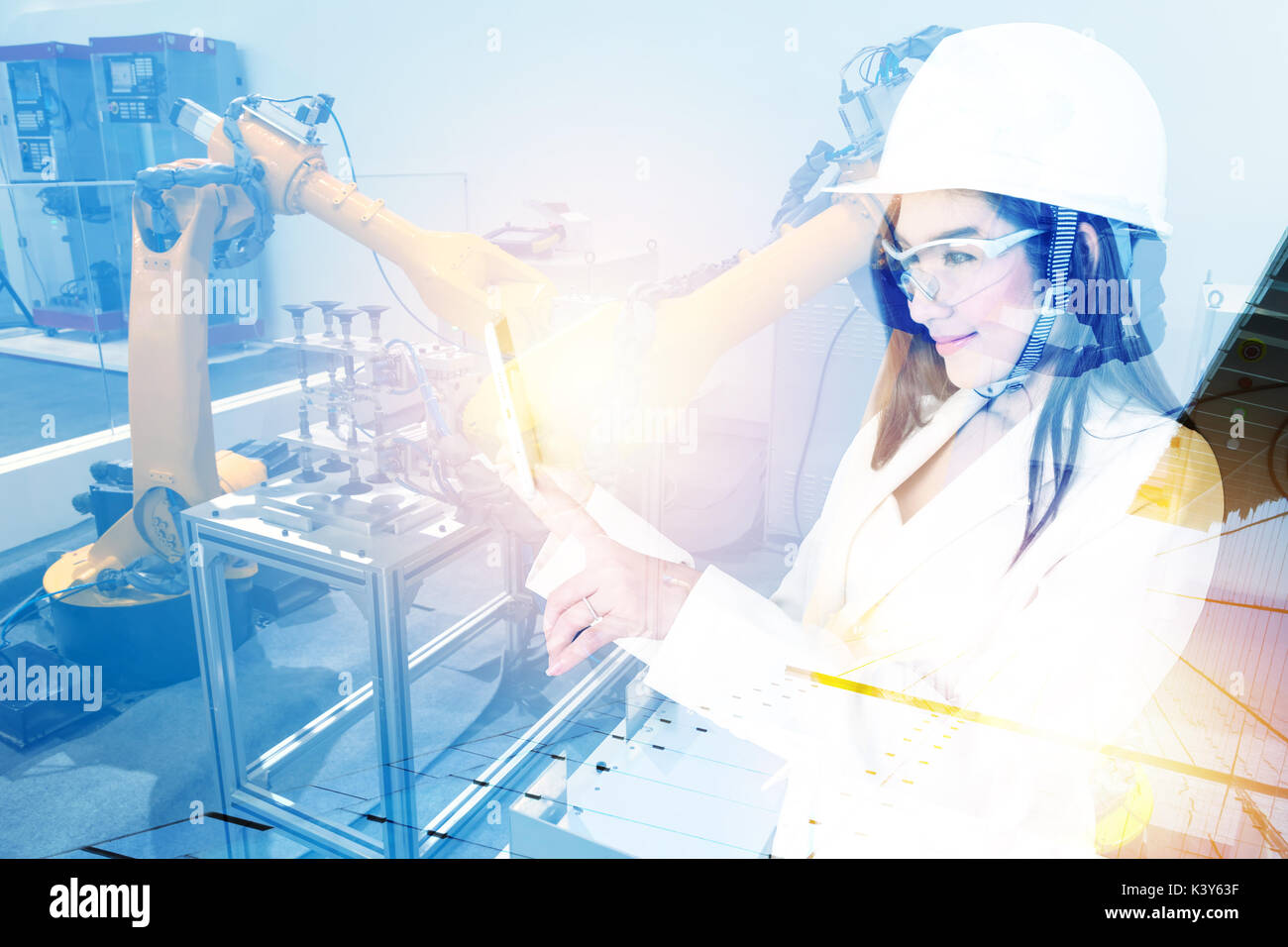 Double exposure of Manufacturing production industrial machine , factory robots arm in smart factory , engineer female using tablet for check monitori - Stock Image