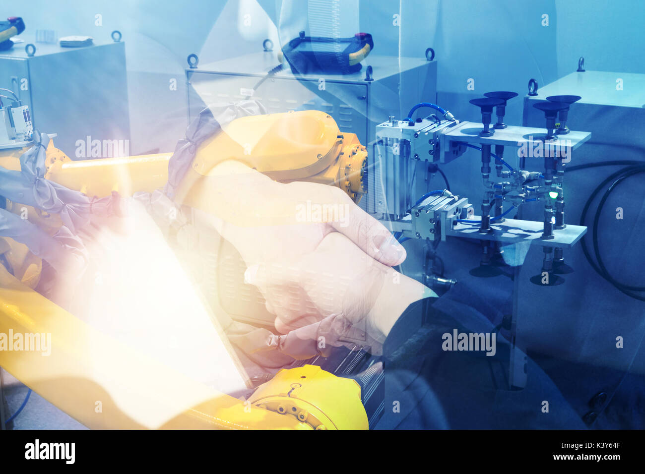 Double exposure of Manufacturing production industrial machine , factory robots arm in smart factory and business people shaking hands with flare ligh - Stock Image