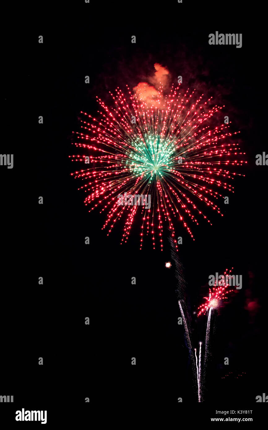 Holiday fireworks display featuring colorful bursting shells. - Stock Image