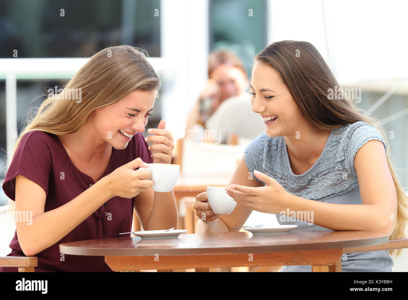 Two best friends laughing loud during a conversation sitting in a restaurant - Stock Image