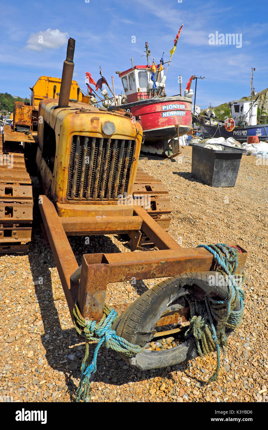 Rusty bulldozer and red fishing boat on Hastings Stade Beach, East Sussex, UK, GB - Stock Image
