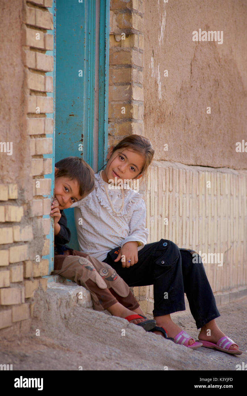Playful Iranian children at the door to their home, Yazd, Iran - Stock Image