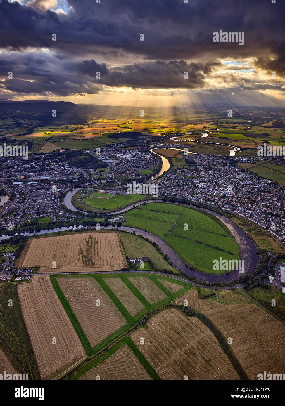 The River Forth snakes into the distance through Stirling as a burst of light  brightens the distant fields, Scotland. Captured from a helicopter - Stock Image