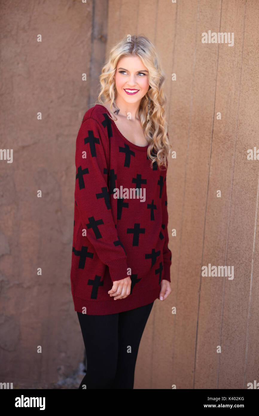 young blonde woman wearing sweater dress and leggings - Stock Image