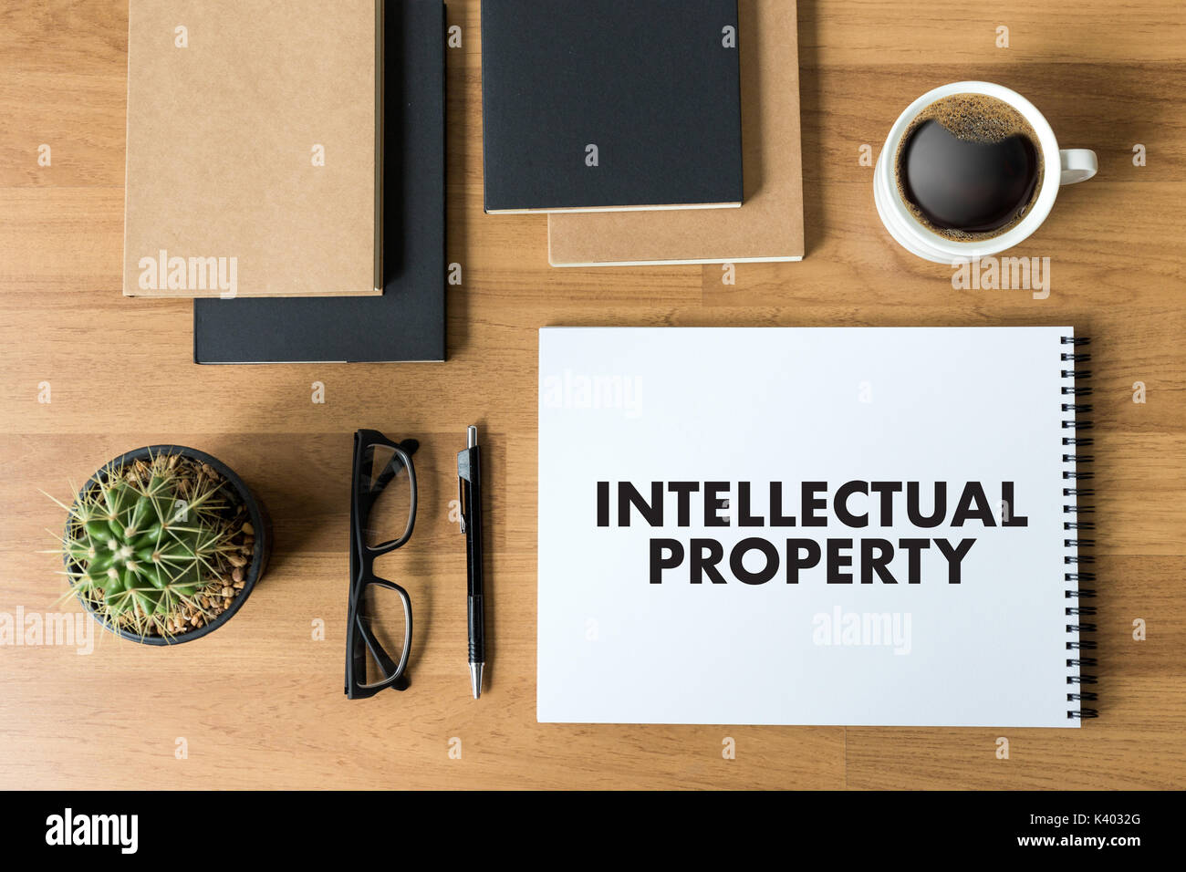 INTELLECTUAL PROPERTY Business team hands at work with financial reports and a laptop - Stock Image