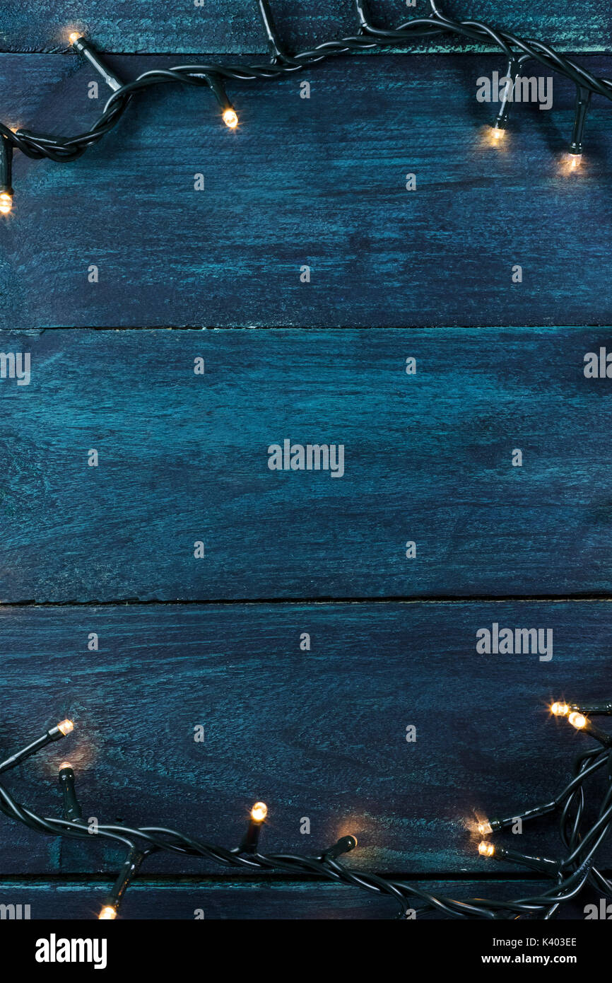 Fairy lights on a dark wooden texture, holiday background - Stock Image