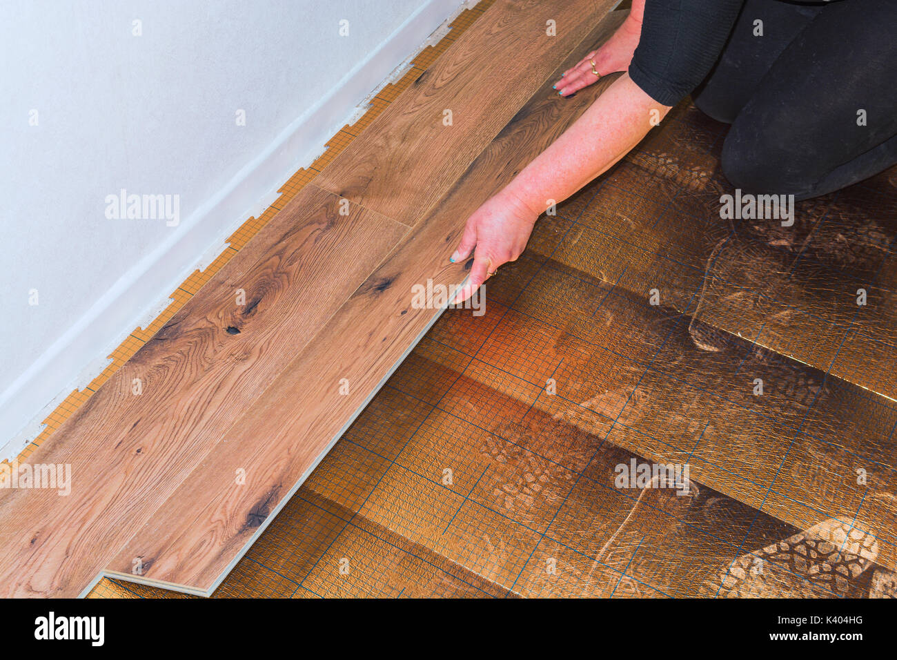 Woman in the laying of plastic laminate or vinyl - Stock Image