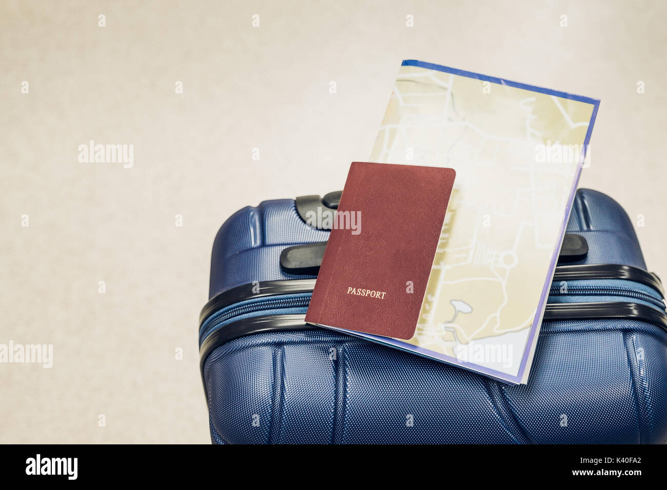 Close up passport and map lay on blue suitcase at airport,travel vacation concept. - Stock Image