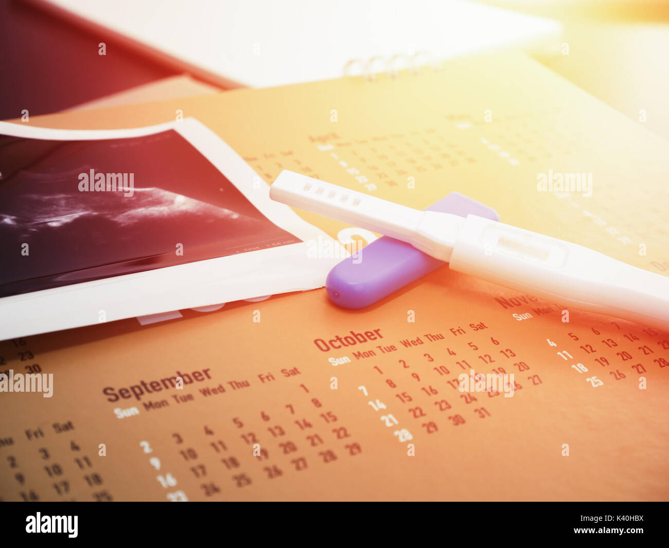 pregnancy test on calendar with ultrasound background Stock Photo