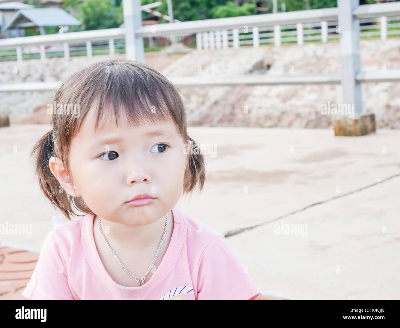 portrait of little girl scowling face playing in the park and soft focus ,asian baby - Stock Image