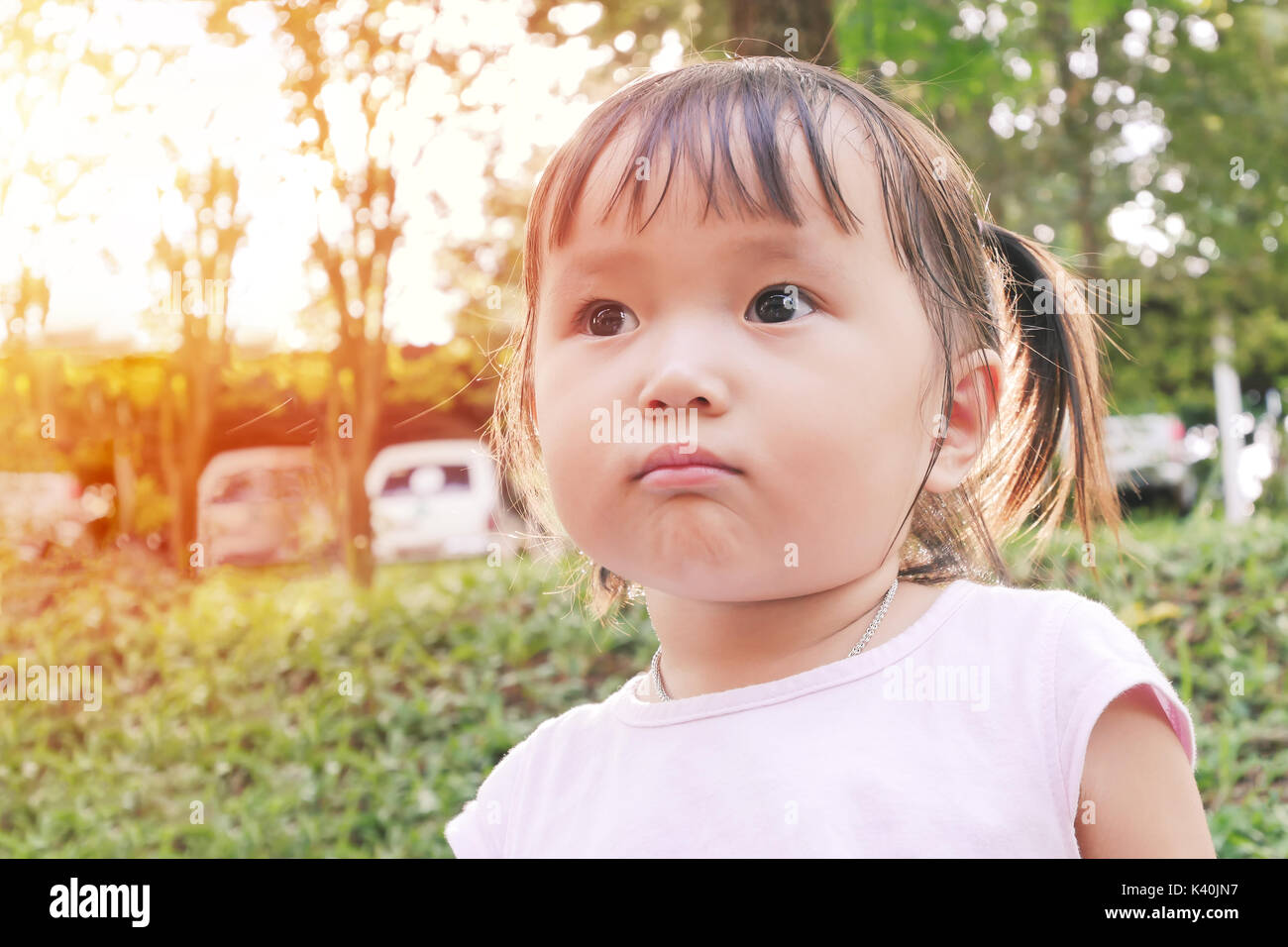 portrait of little girl scowling face playing in the green garden with warm tone and soft focus ,asian baby - Stock Image