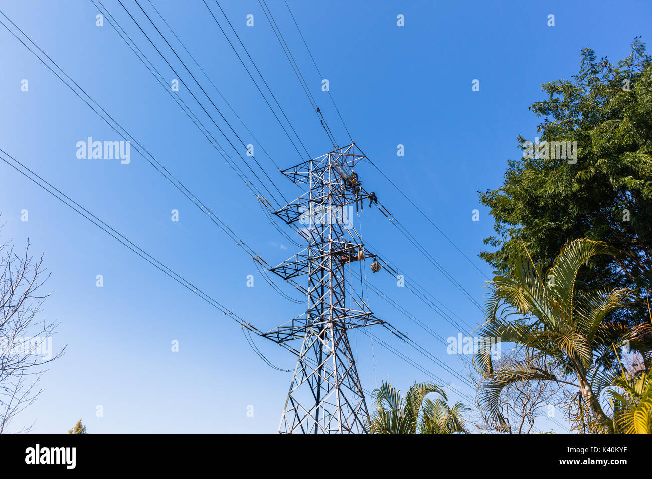 Electricians hanging  high up suspended on electrical steel tower installing new high voltage electricity powerlines. - Stock Image