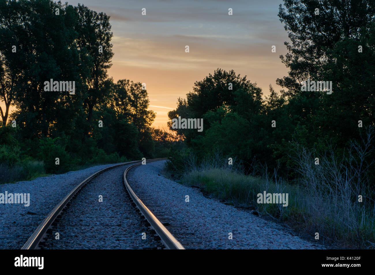 Sunrise in central Iowa over traintracks. - Stock Image