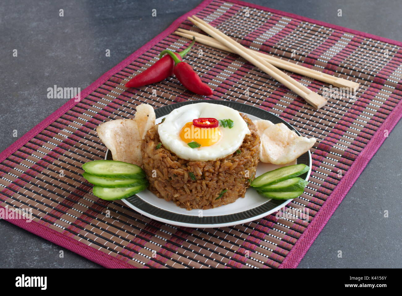 Nasi goreng fried rice with shrimps and egg garnished with fresh cucumber slices and prawn crackers on a plate on a cloth. Asian food - Stock Image