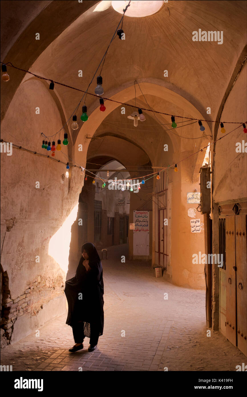 Moody late afternoon light penetrates the bazaar area, Yazd, Iran. Silhouetted Iranian woman in black chador. Stock Photo