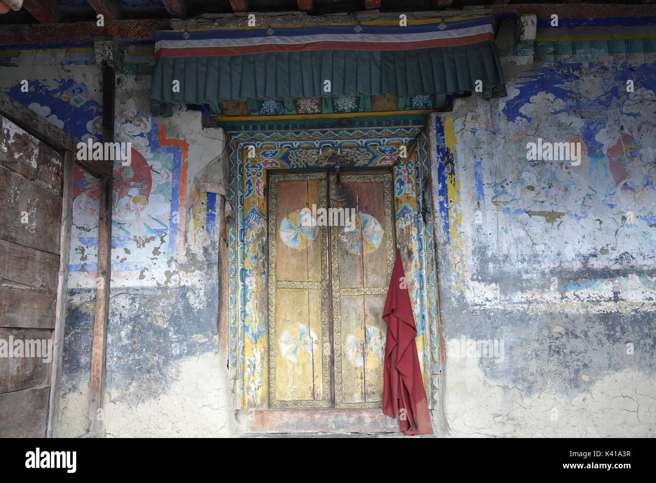 Monks Red Robe Hanging on Door with Tibetan Art Painting at Mu Gompa Monastery, Nepal on Tibetan Border in the Tsum Valley Remote Region - Stock Image