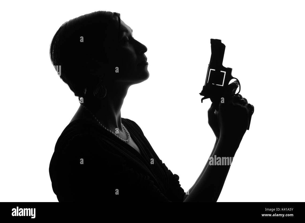 Silhouette of woman private detective with a gun in her hand. Gangster looks like mafiosi and stay side to camera. She wears a dress. Police criminal  - Stock Image