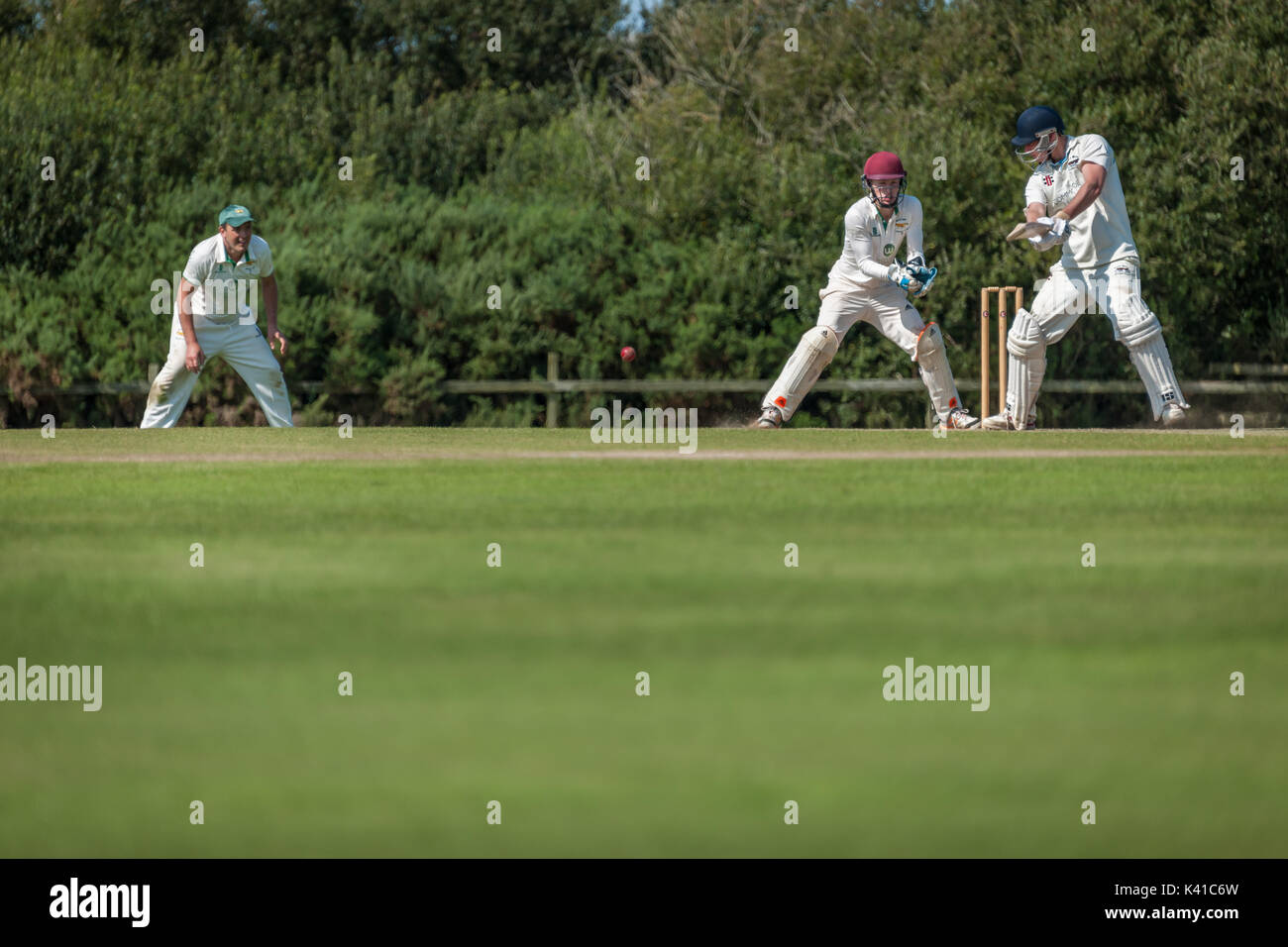 A batsman plays a shot during a Sunday League match between two local Cricket teams. Stock Photo