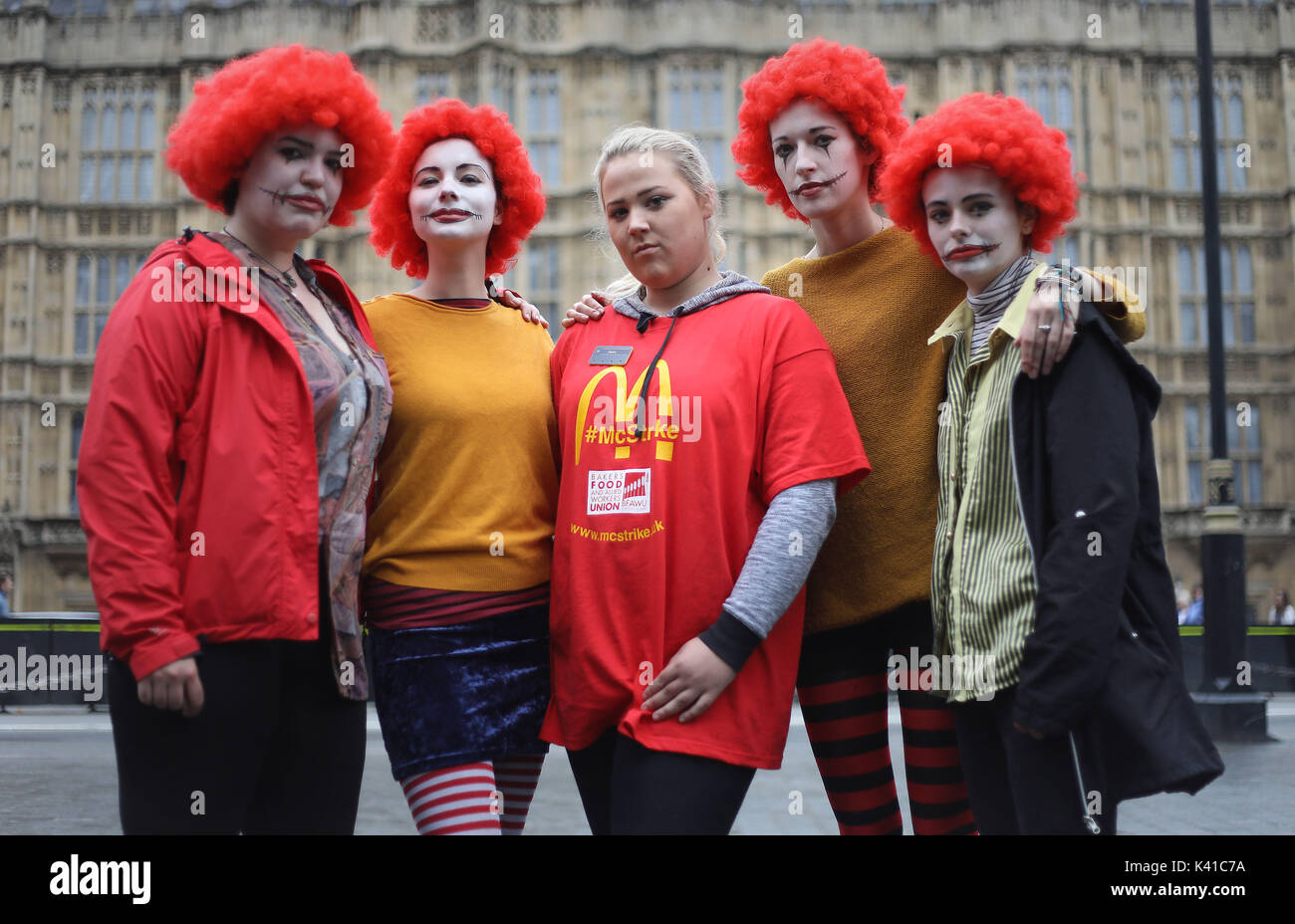 Jess Bower (centre) who is on strike from the McDonald's restaurant in Crayford, SE London, with supporters during a rally at Old Palace Yard, London, after staff voted overwhelmingly in favour of industrial action, amid concerns over working conditions and the use of zero-hour contracts. - Stock Image
