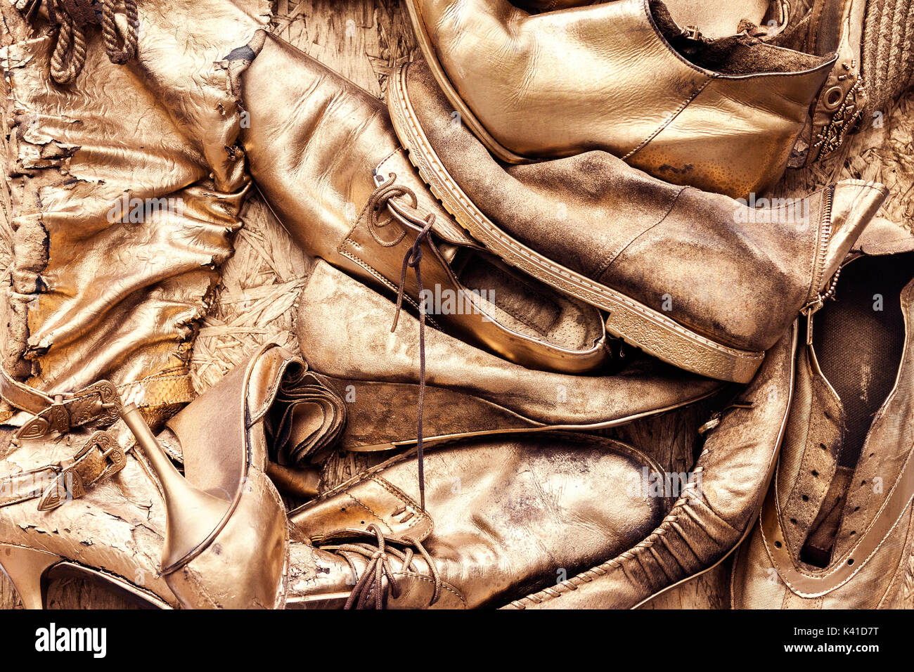Bunch of old worn out shoes and boots painted in golden yellow color - Stock Image