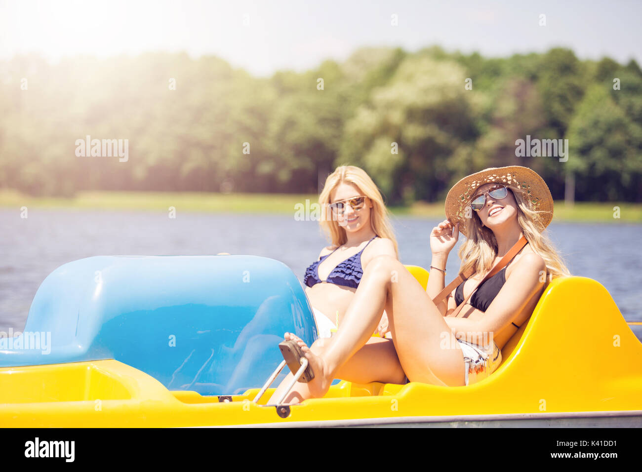 A photo of two beautiful women spending holiday at the lake. They're swimming paddle boat. - Stock Image