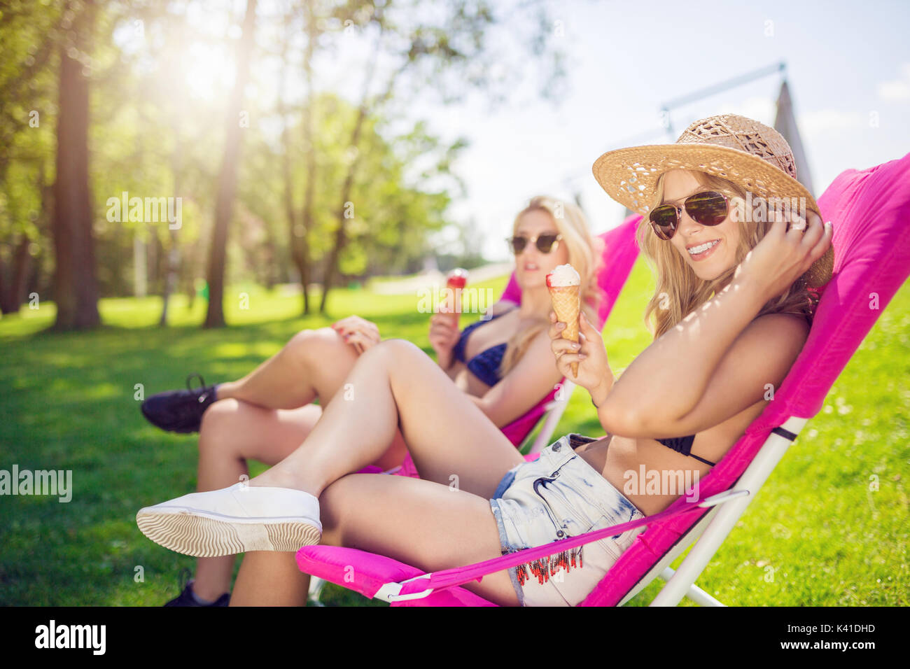 A photo of two female friends spending their free time relaxing at the park and eating ice cream. - Stock Image