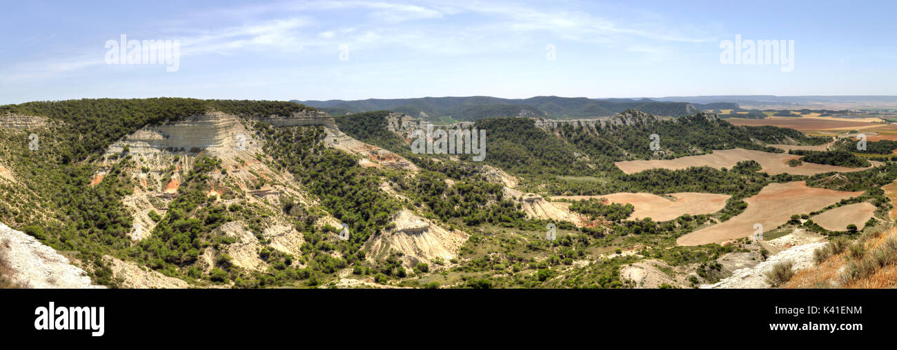 A spanish landscape with cultivated fields, mountains and trees in the Aragon region Stock Photo