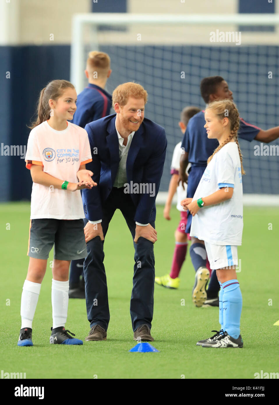 Prince Harry talking to local schoolchildren at the Manchester City Football Club during a Coach Core training session given by apprentice sports coaches in Manchester. - Stock Image