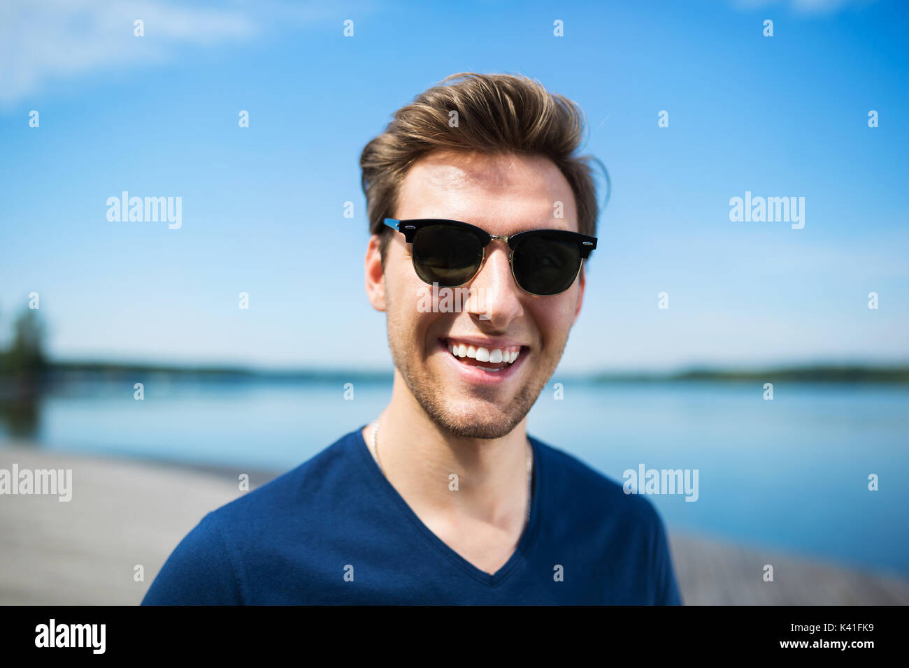 A photo of young, happy man spending his free time at the lake. - Stock Image