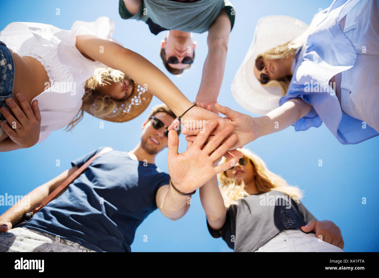 A photo of group of friends standing in a cirlce with their hands put one on another. - Stock Image