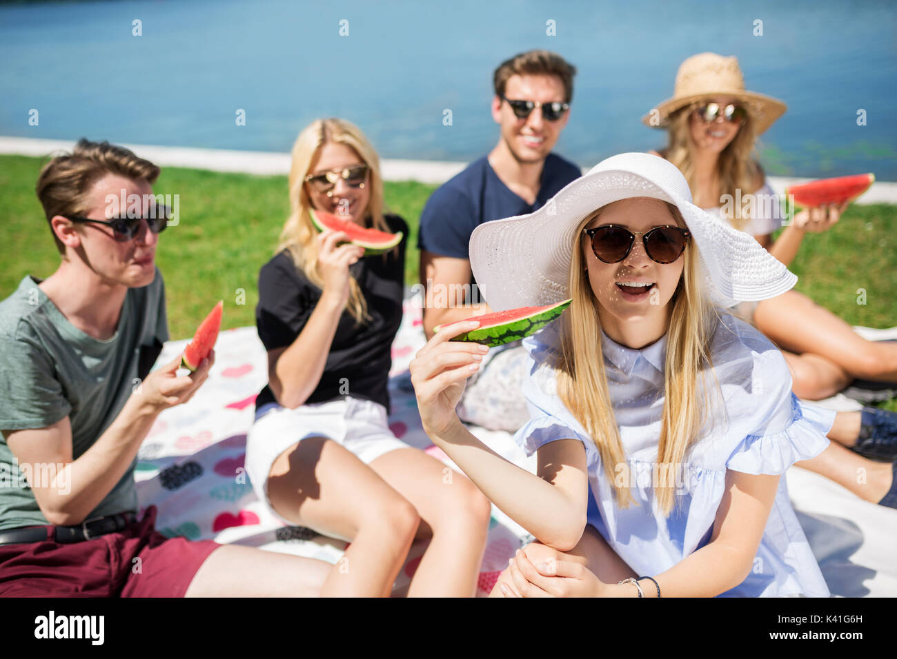 A photo of young, beautiful woman picnicking at the lake with her friends and eating watermelon. They're all having fun. - Stock Image