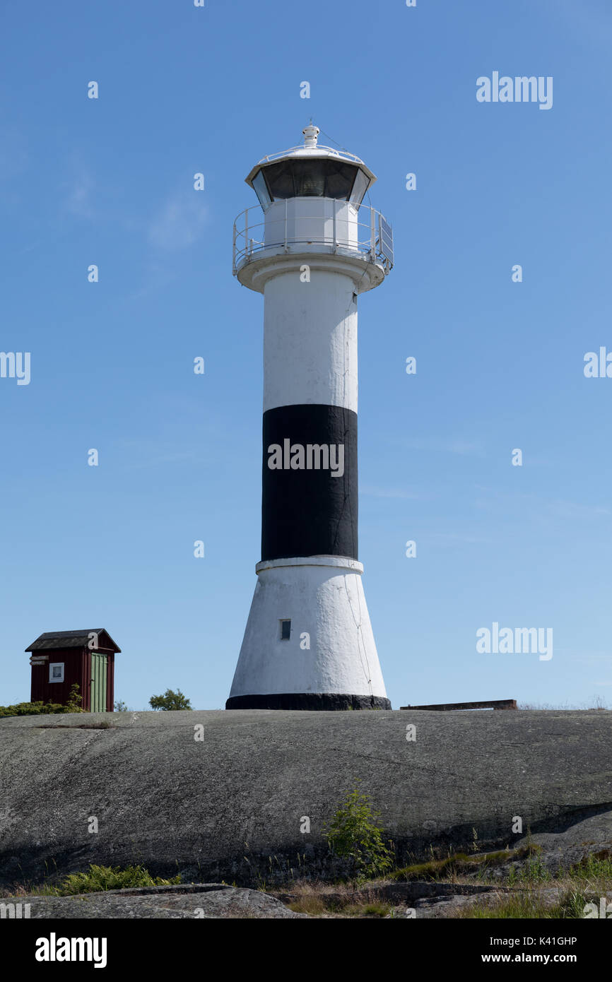Black and white lighthouse in the Stockholm archipelago against a blue sky - Stock Image