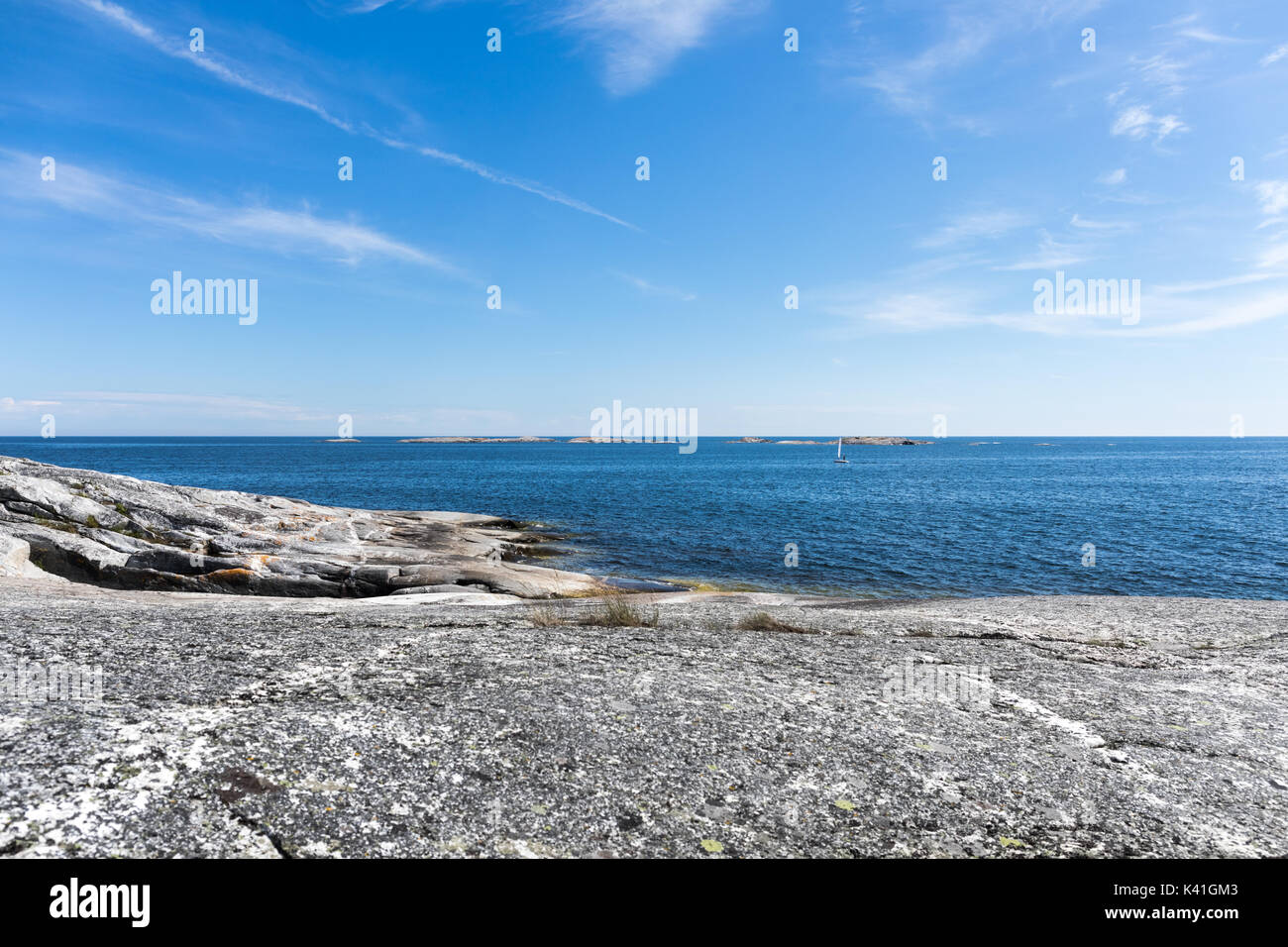 A small dinghy sails along the coastline of an island int eh otuer reaches of teh Stockholm archipelago on a bright sumnmer's day - Stock Image