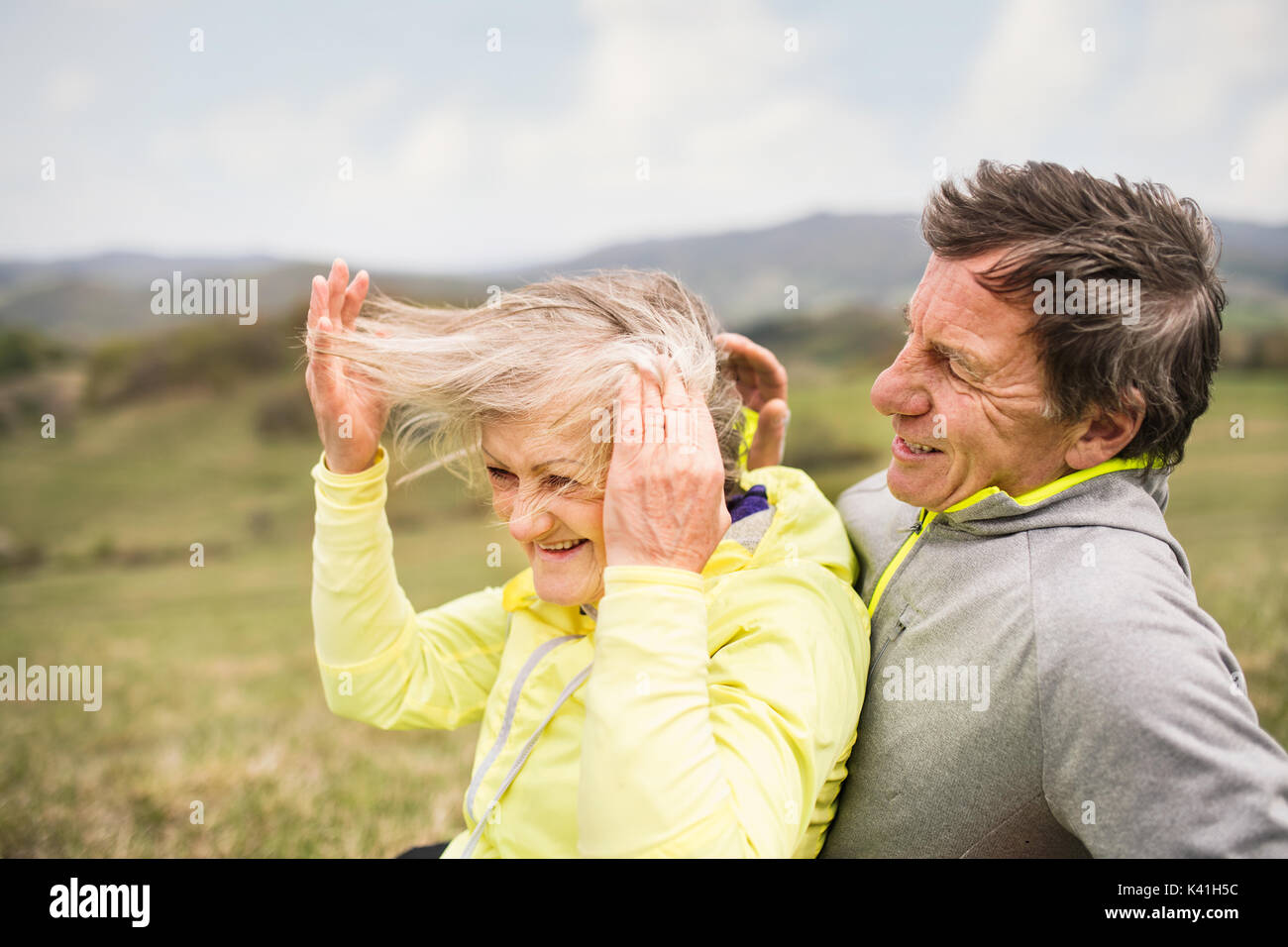 Beautiful senior runners resting outside in sunny autumn nature - Stock Image