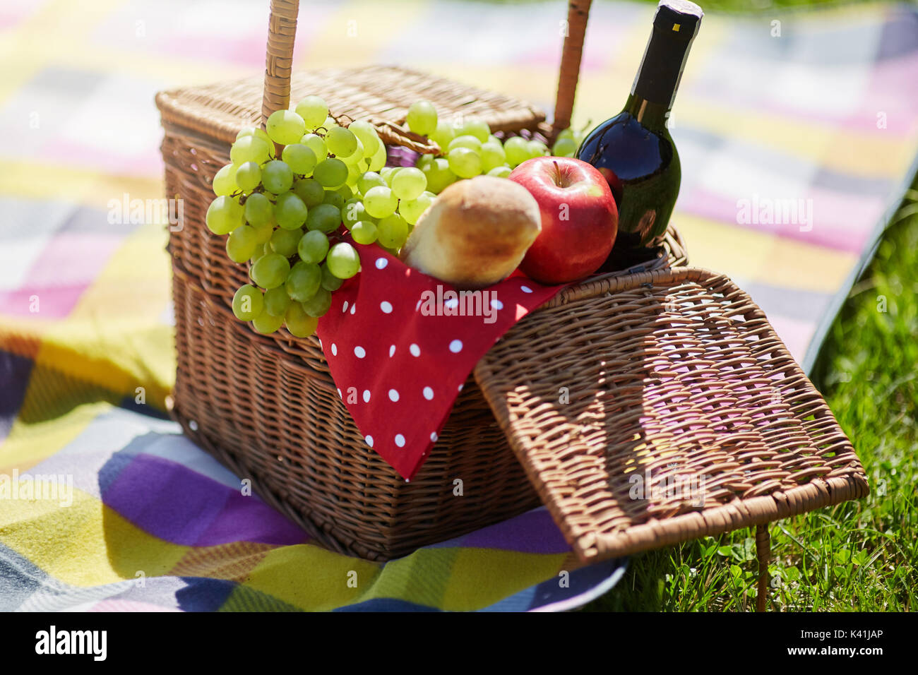 A photo of picnic basket standing on the blanket. It's filled with fruits, bread and wine. - Stock Image