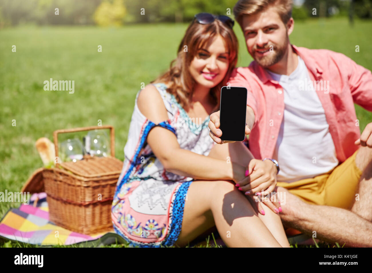 A photo of young, happy couple picnicking on the meadow. The man is holding his newest smartphone. - Stock Image