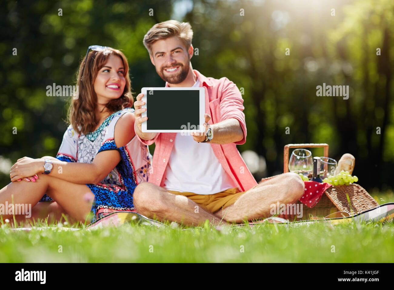 A photo of young, happy couple picnicking on the meadow. The man is holding his newest tablet. - Stock Image