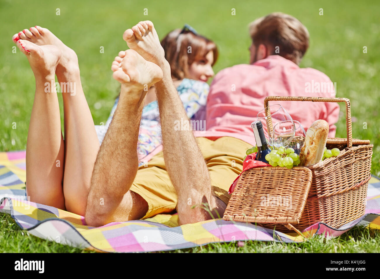 A photo of young couple picnicking on the meadow. They're lying on the blanket and talking. - Stock Image