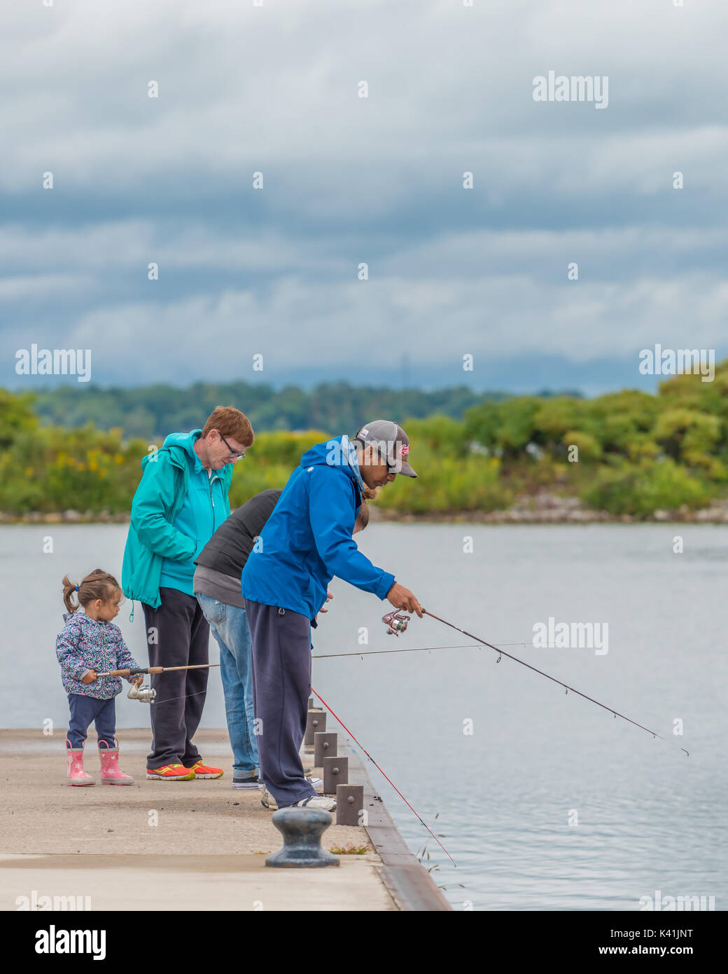 Family members enjoy a day of fishing from the pier in Orillia Ontario Canada. - Stock Image