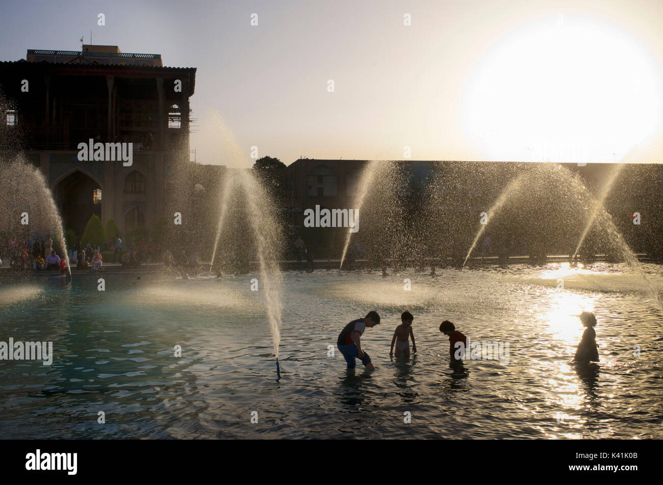 Kids playing in the public fountains in front of Ali Qapu Palace, Imam square. Naqsh-e Jahan  Isfahan city, Iran Stock Photo