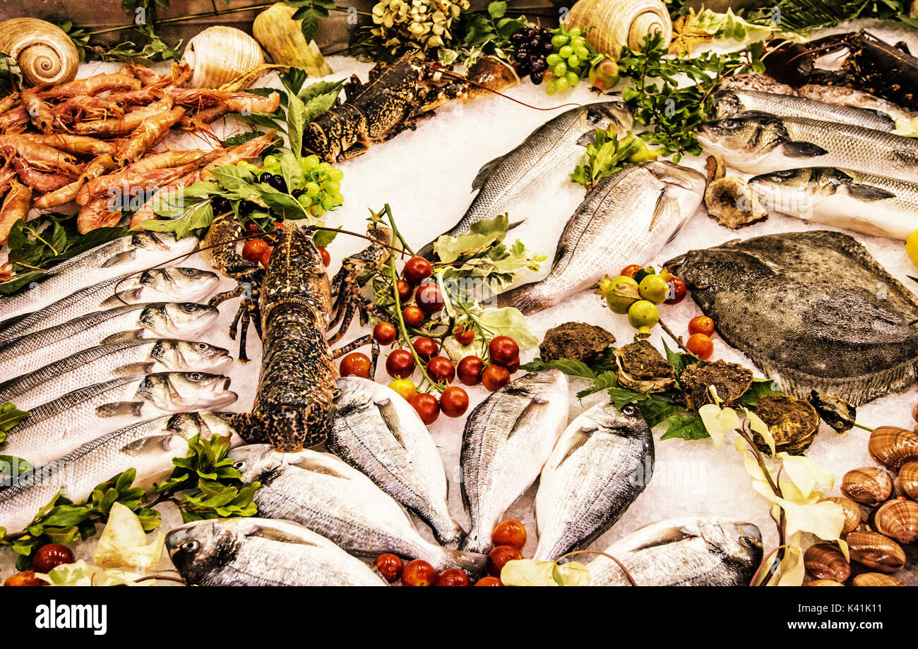 Fresh raw seafoods on counter in restaurant. Food theme. Mediterranean specialties. Yellow photo filter. - Stock Image