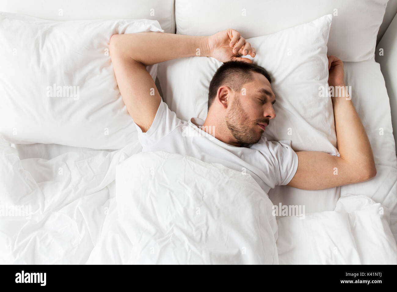 man sleeping in bed at home - Stock Image