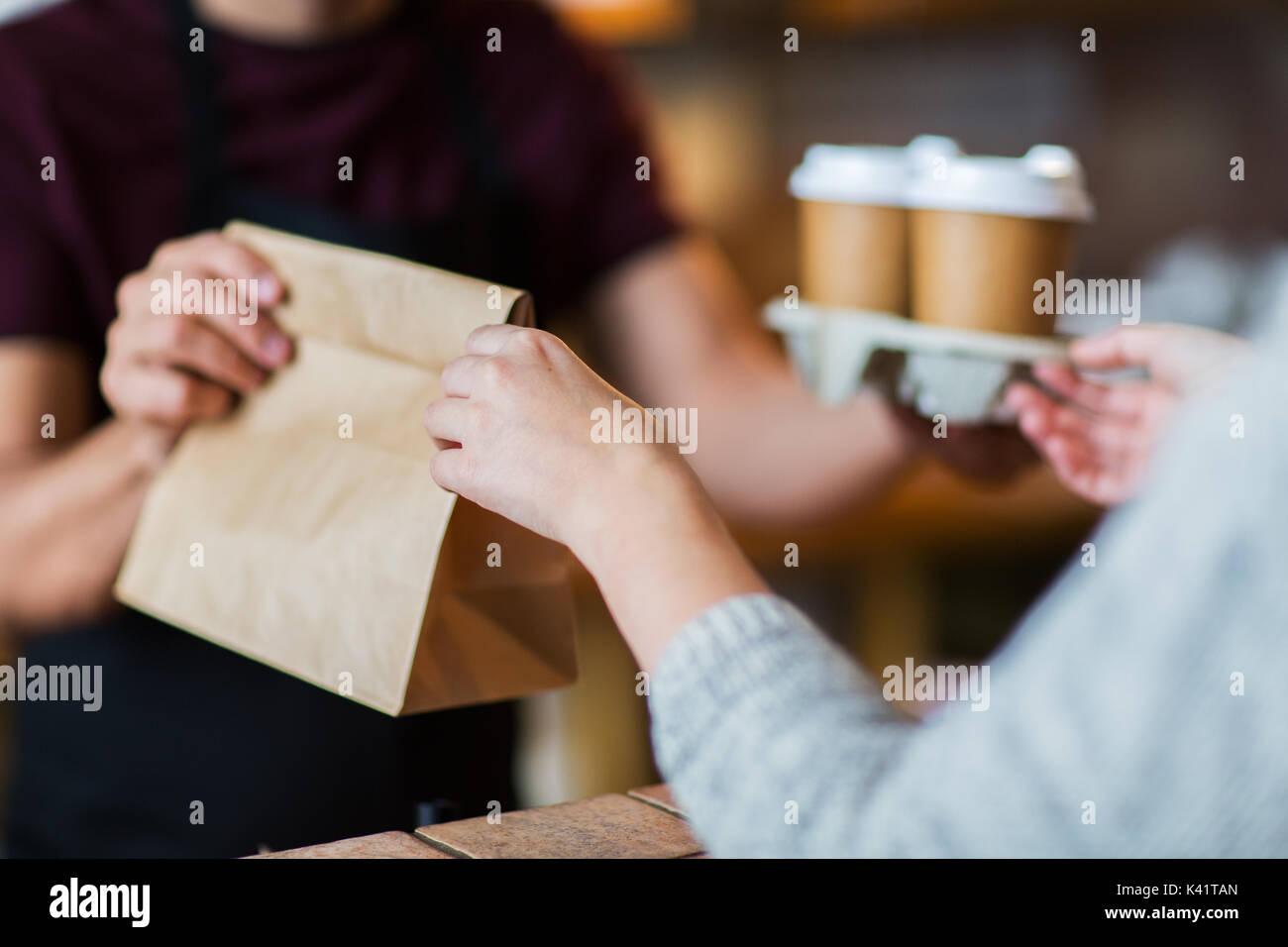 man or bartender serving customer at coffee shop - Stock Image