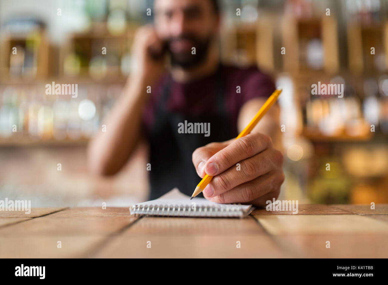 bartender with notebook and pencil at bar - Stock Image