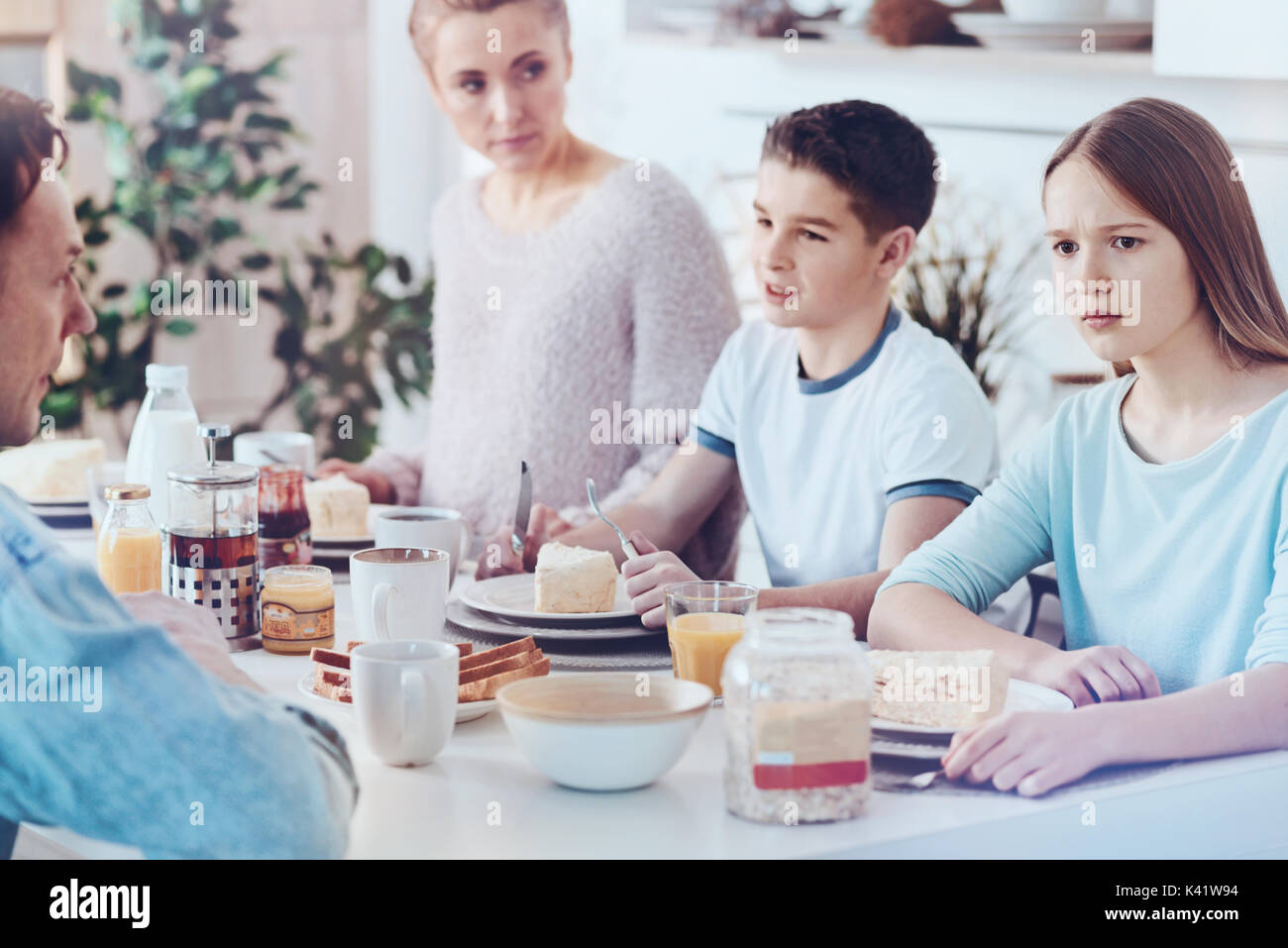 Puzzled teenage girl looking into vacancy during breakfast with family - Stock Image