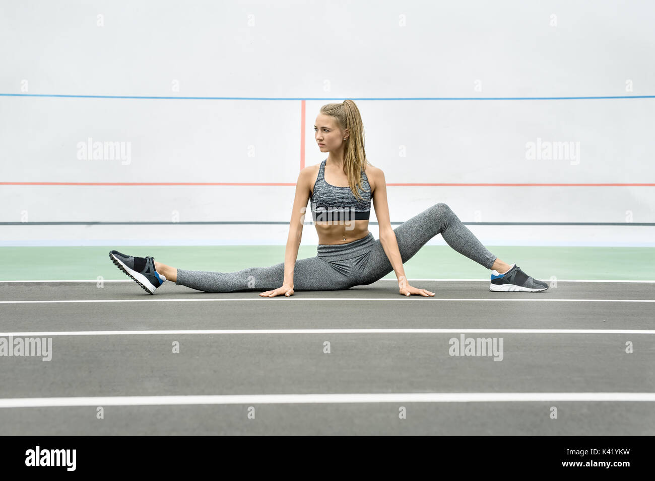 Pretty girl sits on the twine on the cycle track outdoors. She holds her hands on the ground and looks to the side. Her left leg is bent in the knee.  - Stock Image