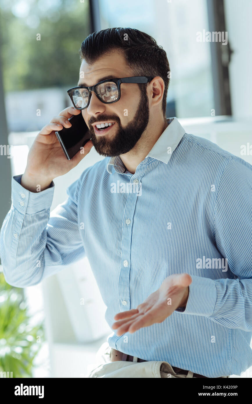 Young businessman arguing with colleague on the phone - Stock Image