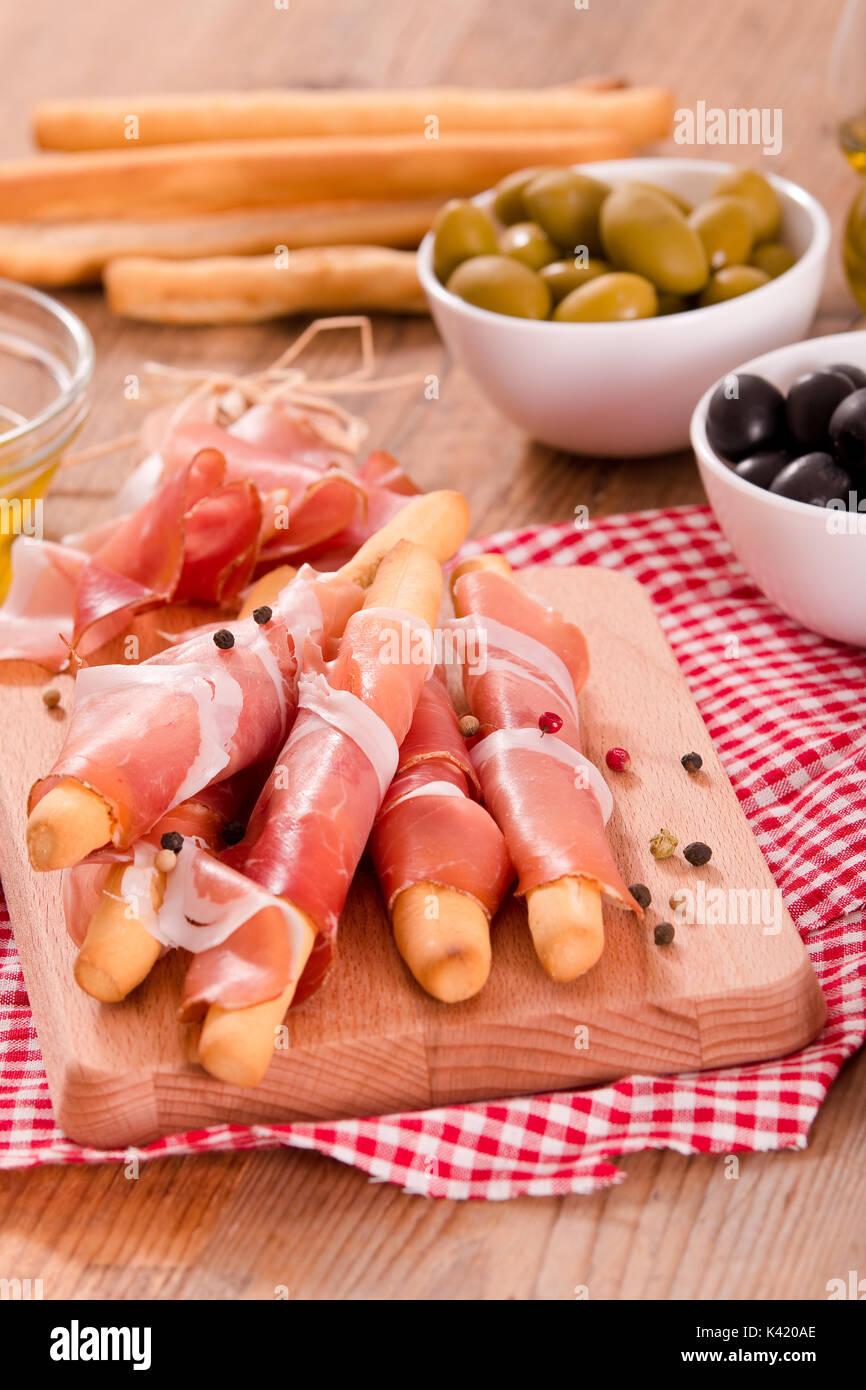 Grissini breadsticks with ham. - Stock Image